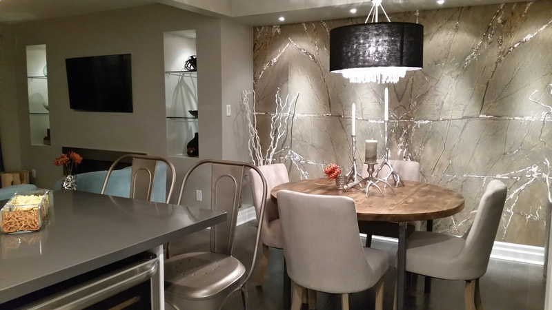 DesignerStone Panels Wall Feature on WNetwork's Property Brothers Episode Nancy and Dave.  Stone is a light brown color called Rainforest Brown and it is shown with a small contemporary dining room table and chairs in front.